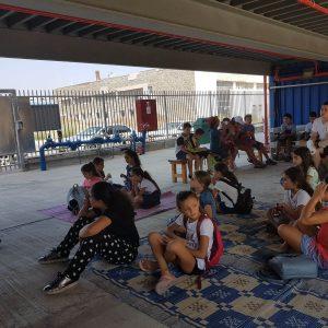 ילדי מתנס שיא רחובות בזמן פעילות, יושבים על מחצלת בחצר המרכז