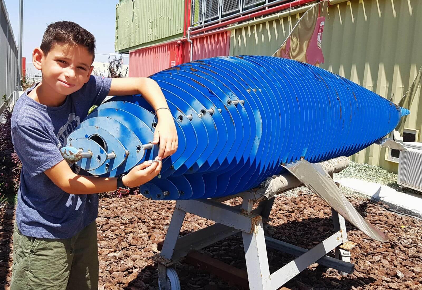 נער צעיר לצד כריש מחומרים ממוחזרים